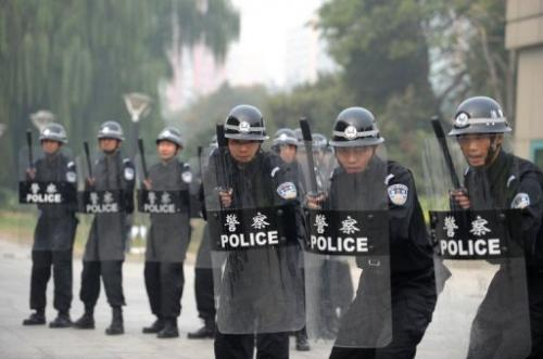 Chinese police crouch behind riot shields during a crowd control drill in Beijing on October 12, 2011