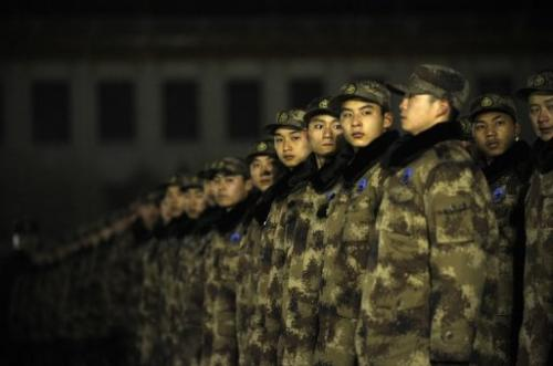 Chinese soldiers prepare to watch the daily flag-raising on Tiananmen Square in Beijing on January 1, 2013