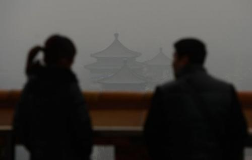 Chinese tourists look at Jingshan Park through thick smog, Beijing on January 31, 2013