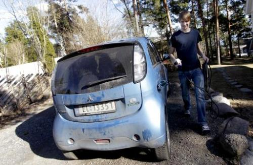Christian Blakseth, who traded his bicycle for an electric car, charges his vehicle's batteries, in Oslo, on April 18, 2011