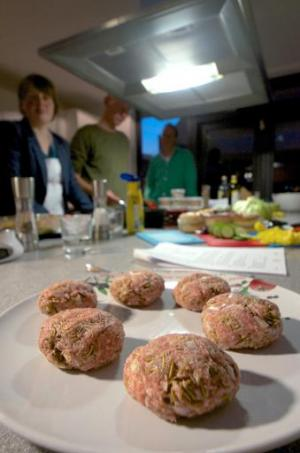Cooking instructor Cecile Lormans (L) and her pupils look at meat balls mixed with insects, to be used for hamburgers, during an