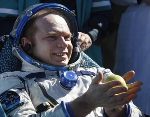 Cosmonaut Oleg Kotov holds an apple after the landing of a Russian Soyuz space capsule near Dzhezkazgan on June 2, 2010