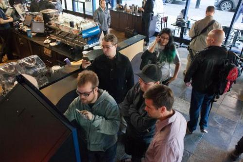 Curtis Machek, left, uses the world's first bitcoin ATM at Waves Coffee House on October 29, 2013 in Vancouver, British Columbia