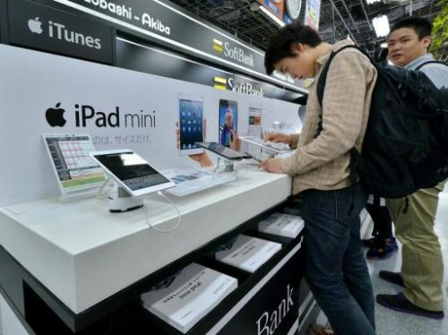 Customers check the Apple's tablet iPads at an electronics shop on May 31, 2013