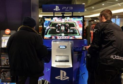Customers have a go on a PlayStation 3 game console on November 27, 2012 in a Paris store