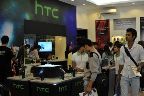 Customers look at HTC handsets on display in a HTC mobile phone shop in Yangon on January 14, 2013