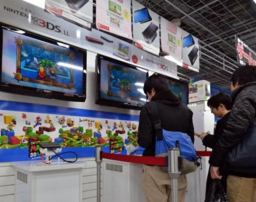 Customers play Nintendo's portable console 3DS LL at an electrics shop in Tokyo on January 30, 2013