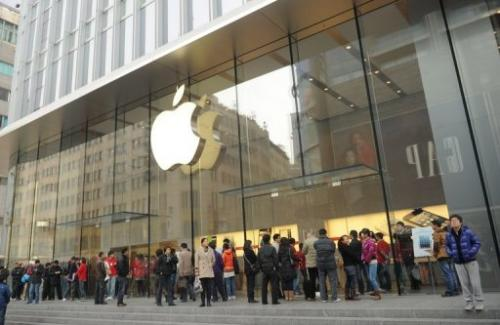 Customers wait for an Apple store to open as = the new