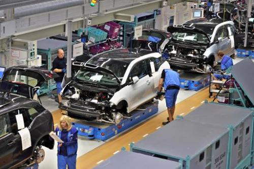 Employees of German carmaker BMW work on the production of the new electrical vehicle i3 at the plant in Leipzig, eastern German