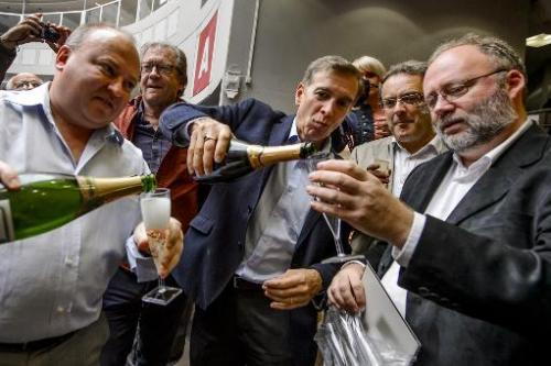 European Organisation for Nuclear Research (CERN) scientists celebrate with champagne after the annoucement of the winners of th