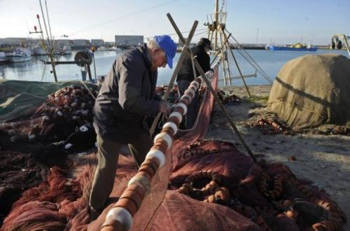Fishermans sew nets next to boats anchored at the fishing port of Barbate, southern Spain, on January 9, 2012