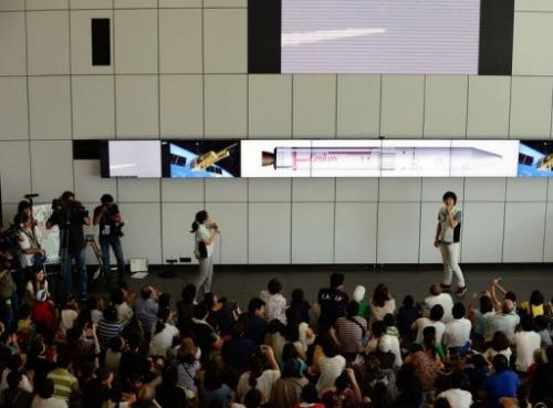 Guests watch a live transmission of the launch of Japan's new solid-fuel rocket in Kagoshima on September 14, 2013