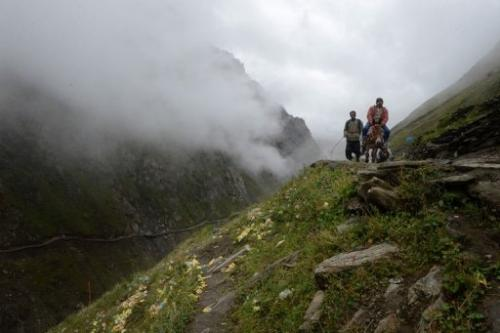 Hindu pilgrims travel past rubbish along the mountain track to the Amarnath cave shrine on August 18, 2013
