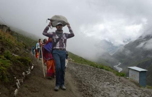 Hindu piligims walk past a latrine along the track to the Amarnath cave shrine on August 18, 2013
