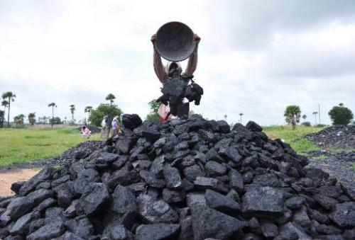 Indian labourers pile coal at a coal field on the outskirts of Hyderabad on September 5, 2012