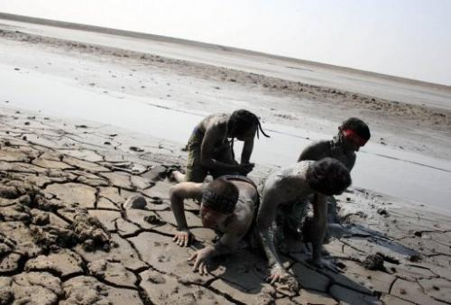 Indonesian activists cover themselves in sludge from a mud volcano during a protest in Porong village on May 29, 2011