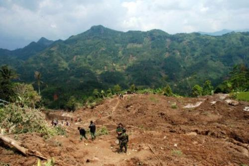 Indonesian search and rescue officers look for victims of a landslide at the Muka Payung village, March 25, 2013