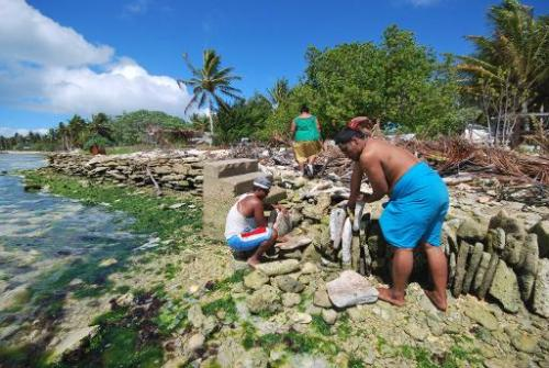 Inhabitants of Kiritimati coral atoll build a stone seawall to struggle against sea level rise cause by global warming, in this