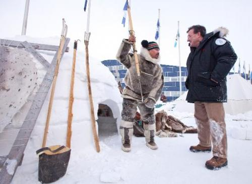 Inuit hunter Pitseolak Alainga (left) explains seal hunting to Canada's Finance Minister Jim Flaherty in Iqaluit, Canada on Febr