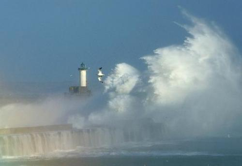 Large waves break against the dyke at the the port of Boulogne, northern France, on October 28, 2013 as storms hit swathes of Eu