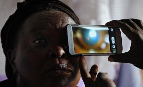 Mary Wambui gets her eyes examined at her home in Kianjokoma village, on August 28, 2013