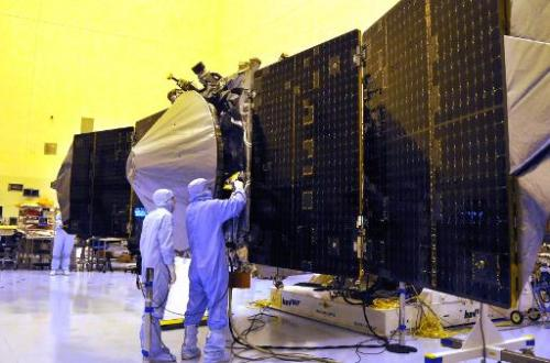 NASA's Mars Atmosphere and Volatile Evolution spacecraft with solar panels extended September 27, 2013 is checked by technicians
