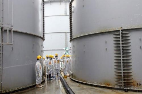 Nuclear inspectors look at contaminated water tanks at the Fukushima nuclear power plant, August 23, 2013