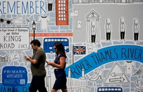 Pedestrians use their mobile phones in central London on August 22, 2012