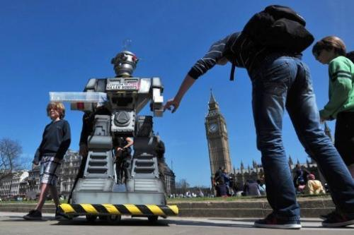 "People look a mock ""killer robot"" in London on April 23, 2013 during the launch of the Campaign to Stop ""Killer R"