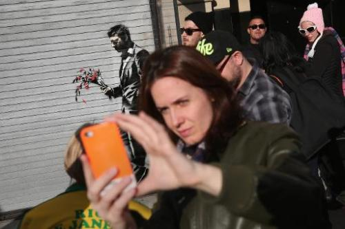 "People take ""selfies"" in front of a painting by British street artist Banksy on a security shutter, on October 24, 201"