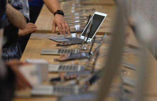 People try out Apple laptops at the opening of the first Apple store in Berlin on May 3, 2013