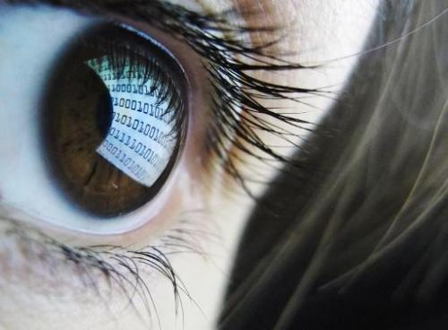 Picture shows binary code reflected from a computer screen in a woman's eye on October 22, 2012
