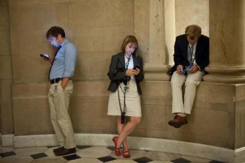 Reporters check their smartphones at the US Capitol in Washington on September 30, 2013