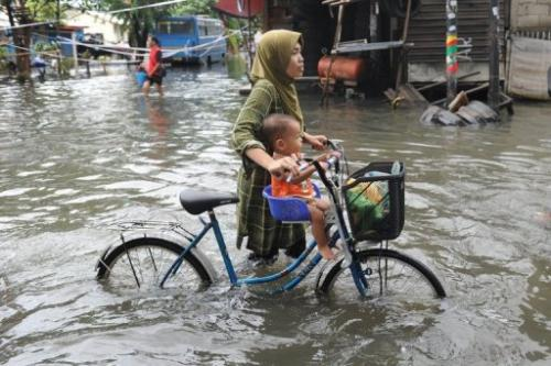 Residents wade through a flooded neighborhood to reach relief distribution centers in Jakarta on January 24, 2013