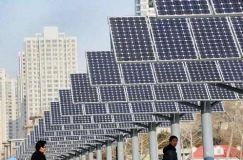 Residents walk past a line of solar power panels in Shenyang, in northeast China's Liaoning province, December 17, 2009