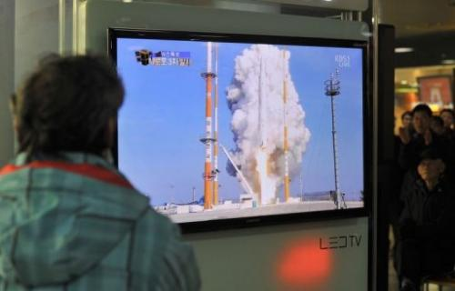 South Koreans watch live footage of the country's rocket launch, at a railway station in Seoul on January 30, 2013