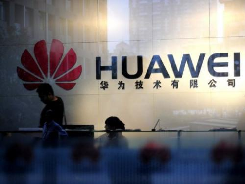 Staff and visitors walk pass the lobby at the Huawei office in Wuhan, central China's Hubei province on October 8, 2012
