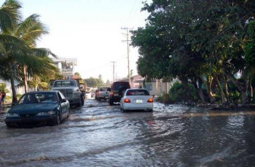 The main the road in Majuro, the capital of Marshall Islands, is seen being flooded from high tides, in December 2008