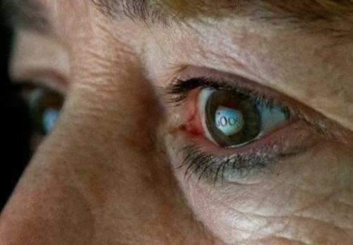 This June 25, 2013 photo illustration shows the Internet search giant Google logo reflected in a woman's eye