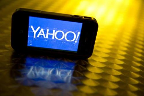 This September 12, 2013 photo illustration shows the newly designed Yahoo logo seen on a smartphone