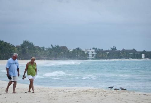 Tourists walk along the beach of Playa del Carmen, near Cancun in Mexico, on October 27, 2011