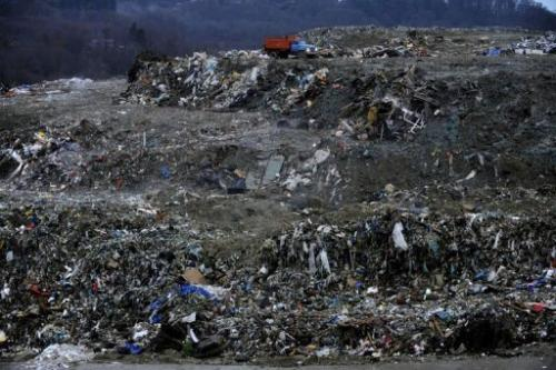 Trucks unload rubbish at a dumping ground near the village of Gorny Vozdukh near Sochi on February 21, 2013