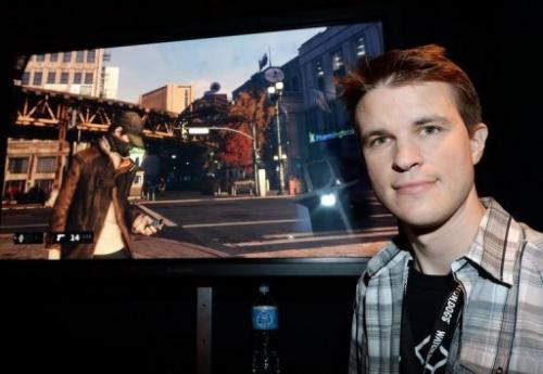 """Ubisoft developer Dominic Guay stands beside a screenshot of """"Watch Dogs"""" at the E3 conference in LA on June 12, 2013"""