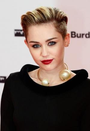 US singer Miley Cyrus poses for photographers on the red carpet as she arrives for the Bambi awards at the Stage theatre at Pots