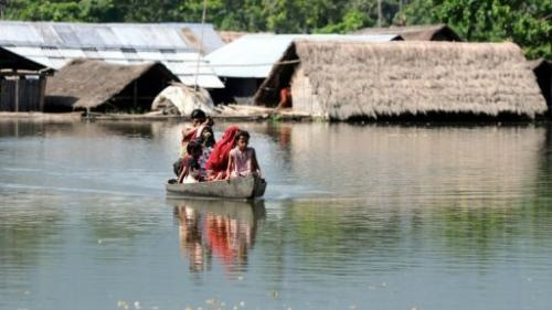 Villagers paddle their boat near submerged houses in a village near Kaziranga National Park on September 27, 2012
