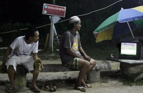 Villagers watch a live broadcast of a football match in Thailand 's Narathiwat province on June 21, 2010