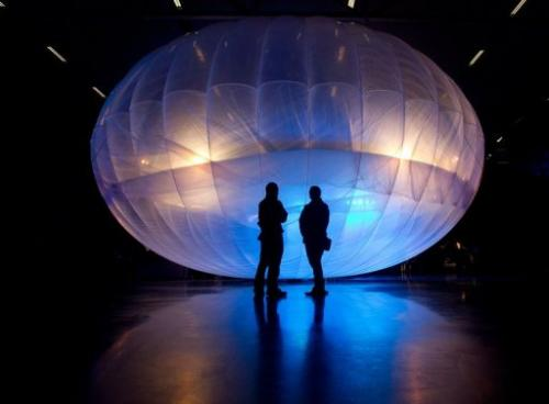 Visitors stand next to a Google Project Loon balloon, in Christchurch, on June 16, 2013