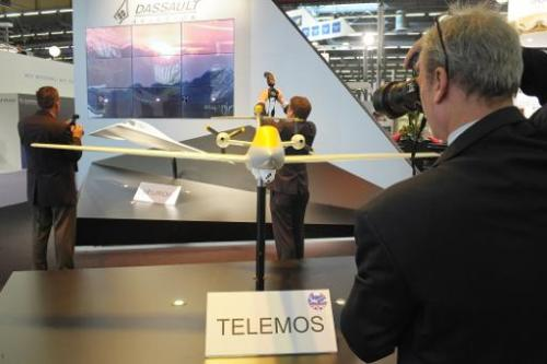 "Visitors take pictures on French Dassault Aviation stand of models of ""Telemos,"" a MALE drone project, at Eurosatory 2"