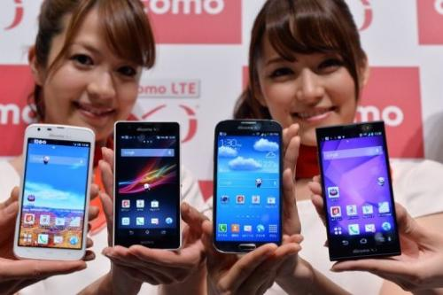 Women show (left to right) Sharp', Sony, Samsung and Fujitsu phones in Tokyo on May 15, 2013