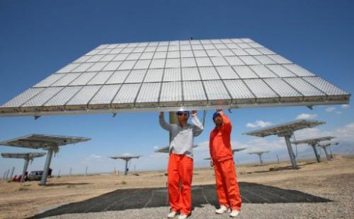 Workers check a solar panel in a field in Hami, China's Xinjiang region, on August 6, 2012